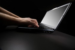typing on the keyboard of a laptop against a black background