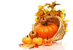 Large pumpkin and small pumpkins in a a wicker basket on a white background