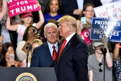 HARRISBURG, PA - APRIL 29, 2017: President Trump and Vice President Pence switch positions on stage at the 100 day mark of their administration. Held at The Farm Show Complex and Expo Center.