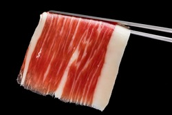 Extreme macro close up of cut piece of cured Spanish bellota pork ham on tweezers.