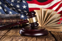 Brown gavel with american flag on wooden table.