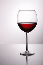 Glass of red wine over light gray white background