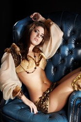 beautiful woman in exotic clothes lies on a chair with her arm over her head