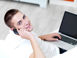 smiling young guy using mobile phone and laptop at home
