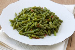 Plate with cooked green beans photographed in vintage style with old dish towel.