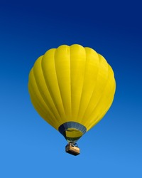 Yellow hot air balloon flying on dark blue sky background