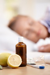 Vitamins, medicines and lemons in front, woman caught cold sleeping in background.?