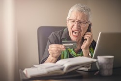 Frustrated senior woman yelling at the bank clerk, dissatisfied with her credit card balance