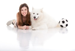 a studio image of a young woman with a white dog, both posing by sitting  their belly, holding hands, smiling, with a football on their side.