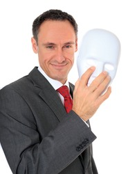 Attractive businessman reveals his face behind a mask. All on white background