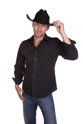 A cowboy in his black shirt and hat showing his small smile and touching his hat.
