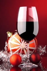 a glass of red wine and Christmas decoration