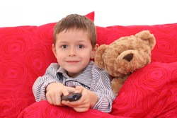5-6 years old boy watching TV in bed