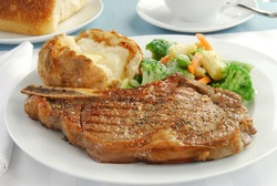 A grilled rib eye steak with baked potato and mixed vegetables