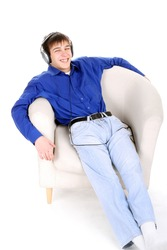 happy teenager in headphones sitting in a chair