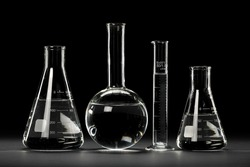 Laboratory glassware over dark background with reflections on table