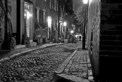 image of an old 19th Century cobble stone road in Boston Massachusetts, lit only by the gas lamps revealing the shuttered windows and brightly lit doorways of the rowhouses on Acorn Street