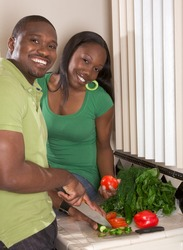 Young black African American couple preparing vegetable salad on kitchen countertop