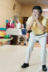 Man covering face at bowling alley