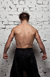 Strong muscular man back at  white wall background