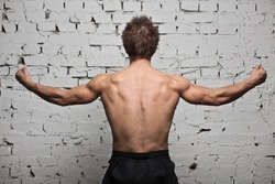 Strong muscular man back at white wall background in hard rage standing