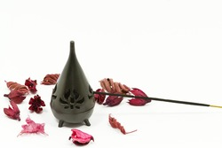 Incense stick in burner with red flower leaves