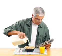 Casually dressed middle aged man pouring milk into his breakfast cereal bowl while reading the morning newspaper. Square format isolated over white.