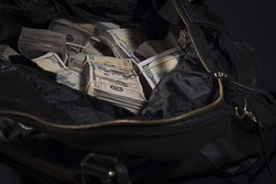 Stacks of money in black bag