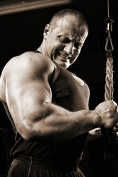 Strong muscullar man training body in gym.