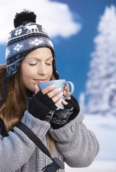 Pretty young girl dressed up warm for skiing wearing cap and gloves drinking hot tea eyes closed front of winter landscape .