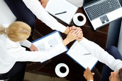 Close-up  of co-workers making pile of hands at meeting