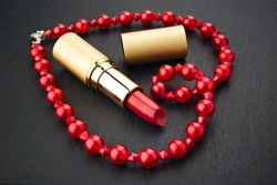 lipstick and red  jewelry in heart shape on black