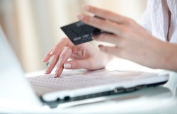 Woman's hand entering data using laptop while holding a credit card in the other hand