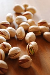 Roasted pistachios on natural wooden table background