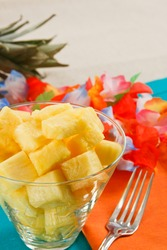 Pineapple salad with a colorful table setting against a beige linen tablecloth