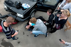 Chaotic scene just after a car crash, with an injured woman lying on the ground, several bystanders providing first aid, and a television reporter with camera capturing the scene, seen from above