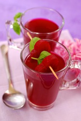 clear beet soup  (  red borscht ) in glass decorated with heart shaped slices