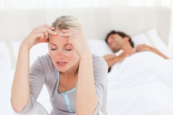 Attractive woman having a headache while her husband is sleeping at home