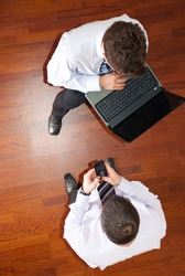 Top view of two  business men using laptop and phone mobile and having conversat