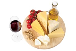 Four popular kinds of cheese, tomatoes and red wine glass on a white background. A shot horizontal, focus in the shot foreground.