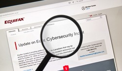 MONTREAL, CANADA - SEPTEMBER, 25 : Equifax Canada home page with information about cybersecurity incident under magnifying glass . Equifax Inc. is a consumer credit reporting agency. Selective focus.