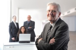 Smiling senior boss with business team on the background