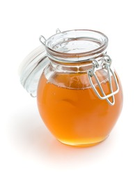 Liquid honey in small glass jar, white isolated background