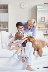 Smiling family pat the dog at home