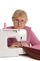 The elderly woman sews on the sewing machine