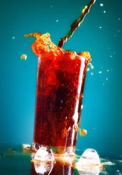 pouring cola in glass over blue background