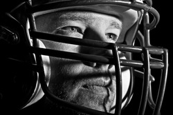 This is a high contrast, black and white image of a young man with an intense look on his face wearing a football helmet. Processed to enhance skin texture.