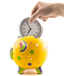 A hand putting a clock into a piggy bank