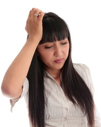 A young woman stressed, overworked, sad or burdened or with a headache.   White background