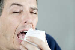 Close-up of a man sneezing.